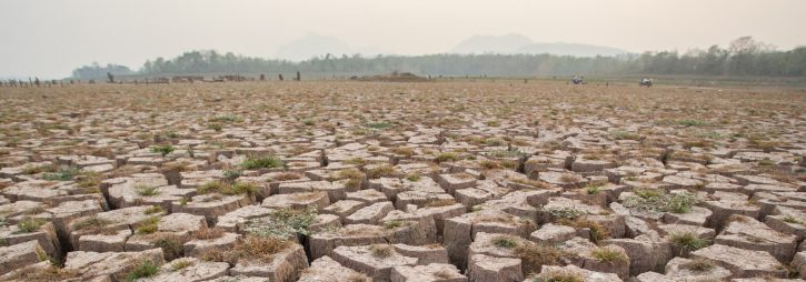 An image of parched earth representing failure of modernity for global social progress.